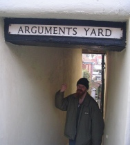 "mans stands with raised fist under sign ""arguments yard"""