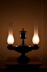 oil lamp with two globes lit on desk in dark room