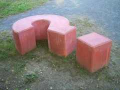 red concrete blocky question mark sculpture sitting in grassy path