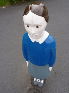 child statue with blank expression, blue shirt, gray skirt standing on concrete