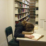 woman studying in library plants face in book on desk