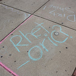 "Chalk writing on sidewalk: ""Rhet-oric?"""