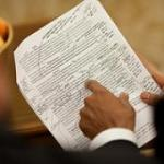 President Obama's left hand points to type written page with hand written annotations
