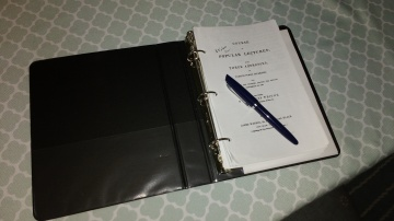 black three ring notebook opened to Wright title page with pen
